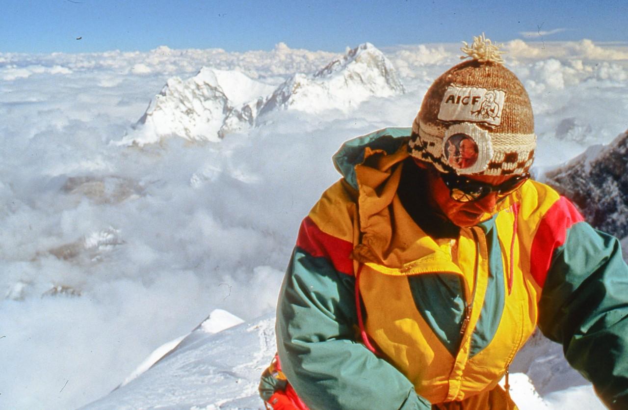Marc-sous-le-sommet-de-lEverest-avec-AICF-et-le-macaron-du-Dala-lama
